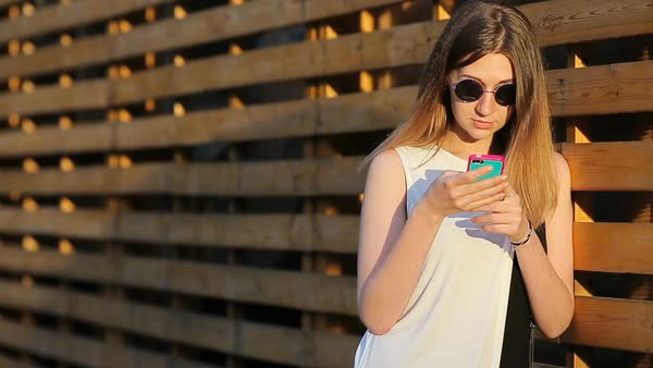81e3e30858 Beautiful girl weared in sunglasses leaning against a wooden wall and using  a smartphone in a