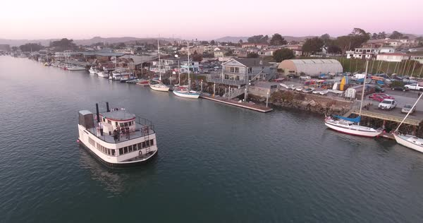 Aerial shot lowering in front of small boat in Morro Bay at Sunset Royalty-free stock video