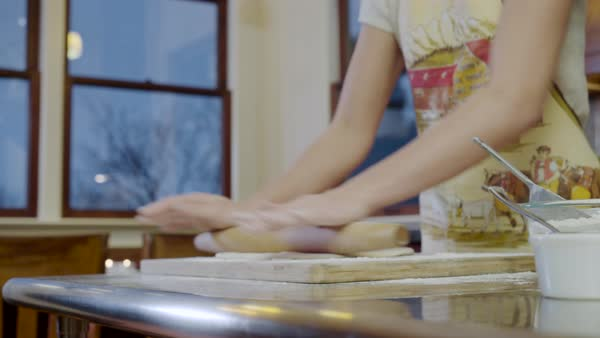 Medium shot of a woman rolling dough in a kitchen Royalty-free stock video