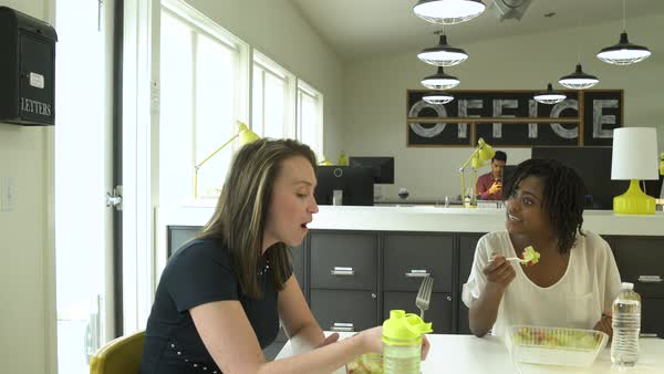 Two young women having lunch in an office Royalty-free stock video