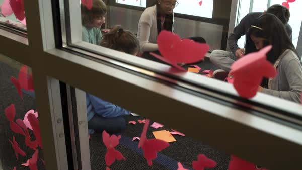Students decorating their school with butterfly cutouts Royalty-free stock video