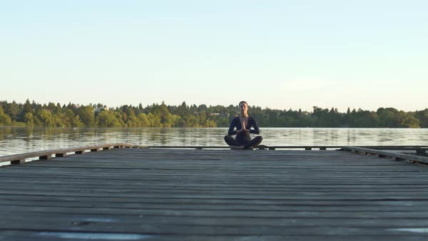 A young woman meditating on a dock Royalty-free stock video