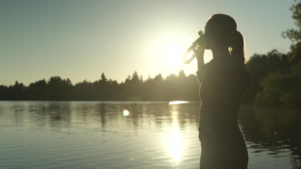 A young woman drinking from a bottle by a lake after exercising Royalty-free stock video