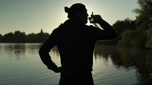A young man drinking from a bottle by a lake Royalty-free stock video
