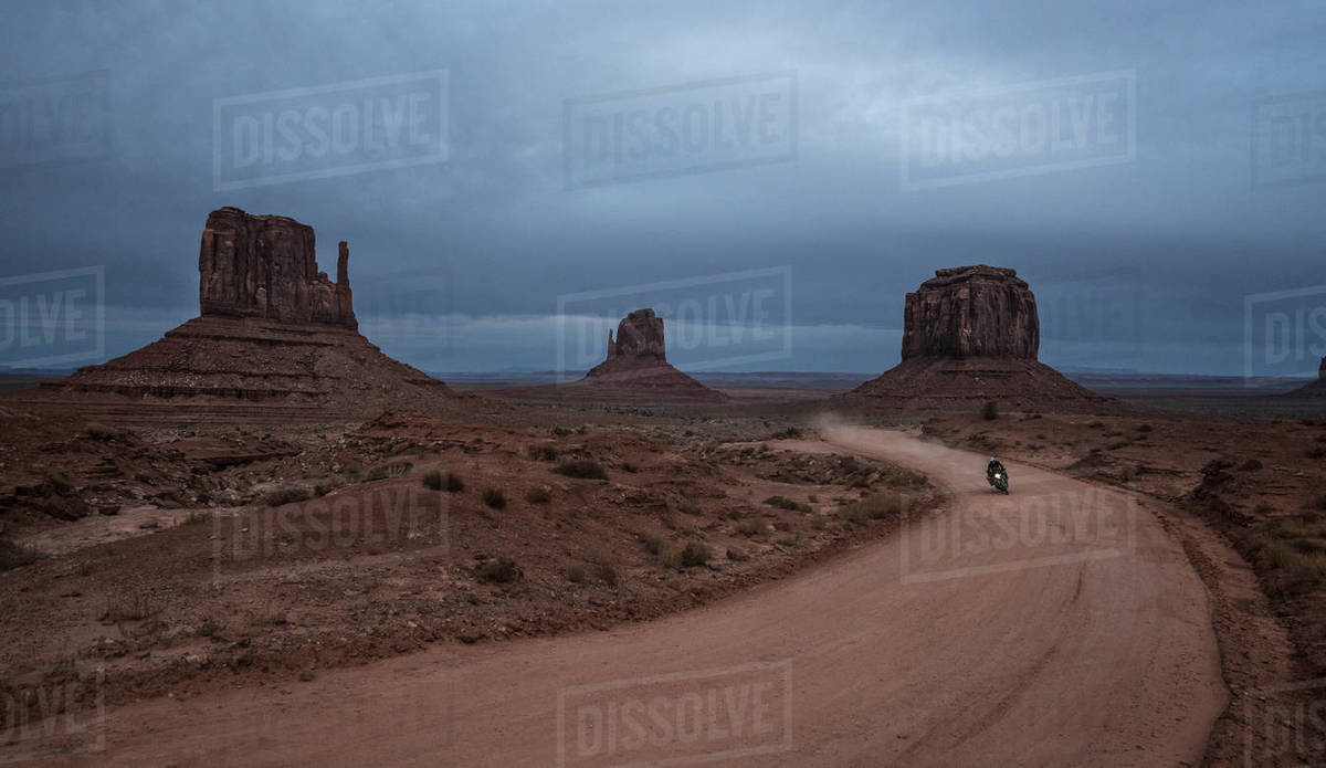 Woman riding motorbike on dirt road passing through desert Royalty-free stock photo
