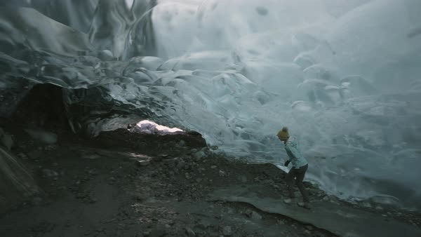 Hand-held shot view of a woman walking in the Mendenhall Ice Caves Royalty-free stock video