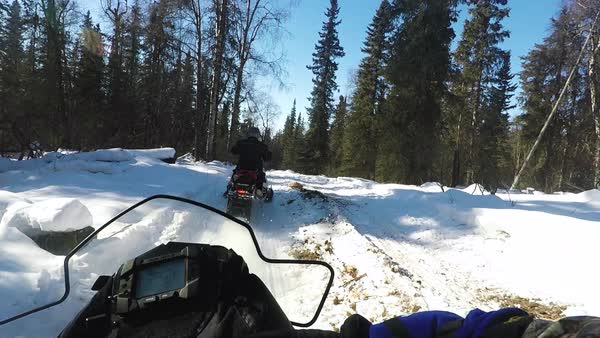 Hand-held shot view of two men riding on snowmobiles Royalty-free stock video