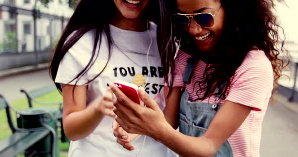 Two pretty vivacious young woman in trendy sunglasses standing close together laughing at a mobile phone as they read a text or multimedia message Royalty-free stock video