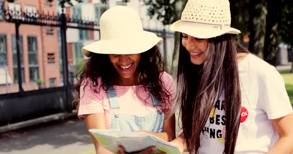 Smiling diverse female friends look at a map while wearing light colored straw hats Royalty-free stock video