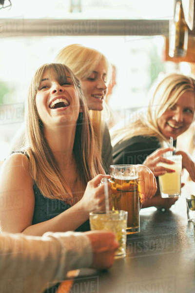 Sweden, Women laughing and drinking beer in bar Royalty-free stock photo