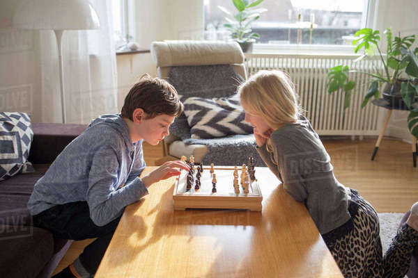 Sweden, Boy (12-13) and girl (10-11) playing chess in living room Royalty-free stock photo