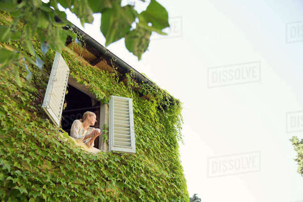 Italy, Tuscany, Dicomano, Woman looking out from window of overgrown house Royalty-free stock photo