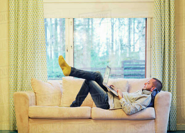 Finland, Man lying on sofa and using laptop Royalty-free stock photo