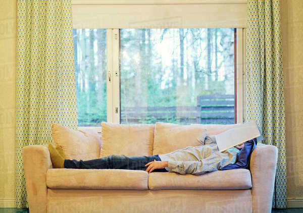 Finland, Man lying on sofa with laptop on face Royalty-free stock photo