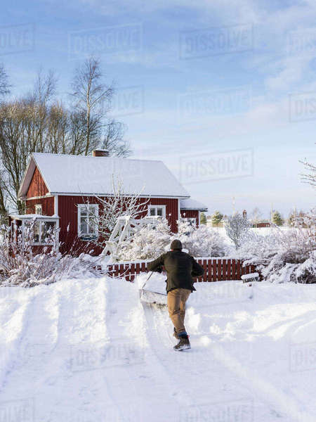 Finland, Pohjanmaa, Pietarsaari, Kruunupyy, Man cleaning yard with snow pusher Royalty-free stock photo