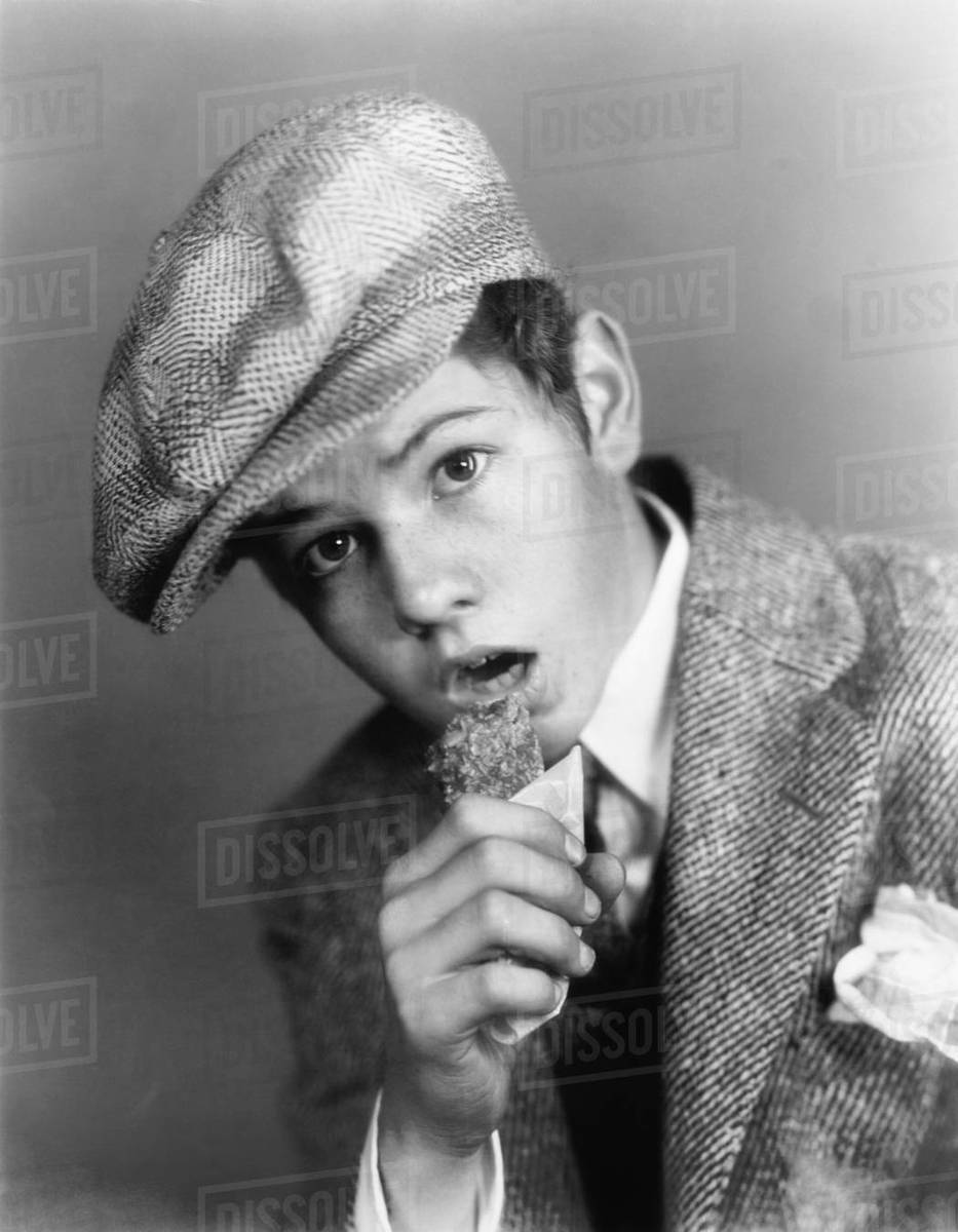 022bfc81 Portrait of a boy with a hat eating a candy bar - Stock Photo - Dissolve