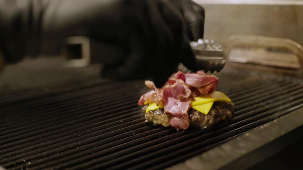 Hand-held shot of a person topping a hamburger patty with bacon on a grill Royalty-free stock video