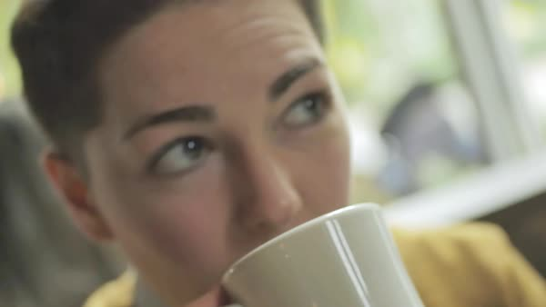 Hand-held shot of a genderqueer person drinking from a mug in a cafe Royalty-free stock video