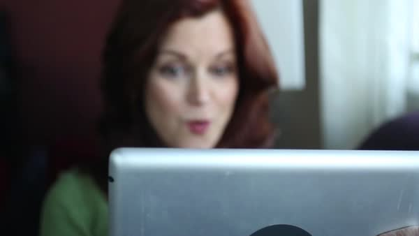 Hand-held shot of a woman smiling and using a tablet at home Royalty-free stock video