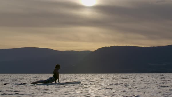 A young woman doing yoga on a paddleboard in Okanagan Lake at sunset Royalty-free stock video