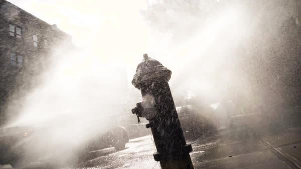 An establishing shot of a fire hydrant spewing water into the street in slow motion Royalty-free stock video