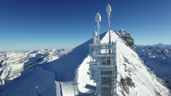 Aerial view of radio antenna in snow covered mountain environment Royalty-free stock video