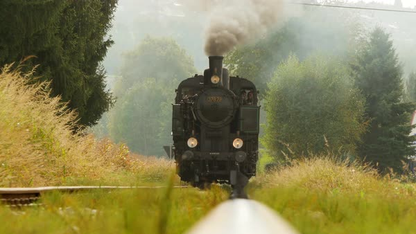 Industrial steam engine train locomotive riding on railroad track in the countryside Royalty-free stock video
