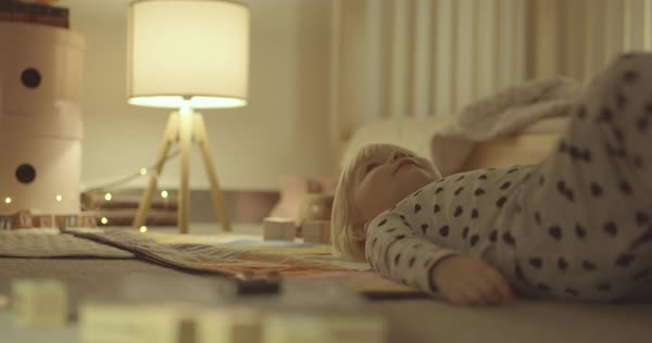 Hand-held shot of a little girl in pajamas lying on floor Royalty-free stock video