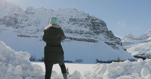 Slow motion shot of a woman taking photos on a beautiful winter day in the mountains Royalty-free stock video