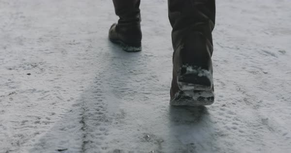Tracking shot of a man's feet as he walks on a snowy road Royalty-free stock video