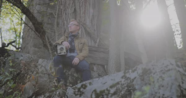 Hand-held shot of a man sitting on a rock with a camera Royalty-free stock video