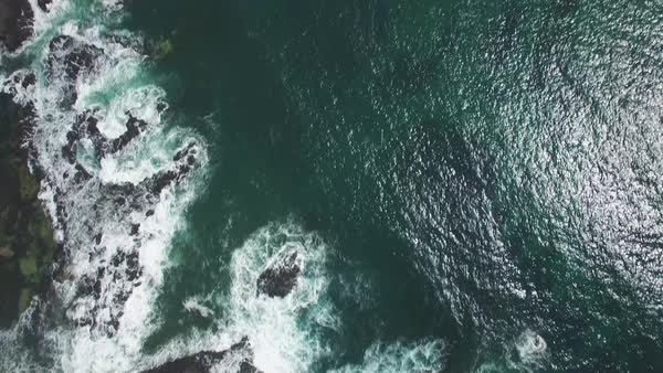 Forward flight looking straight down at ocean waves crushing on rocks and tilting the camera to reveal the horizon and Round Island.  Phillip Island, Victoria, Australia Royalty-free stock video