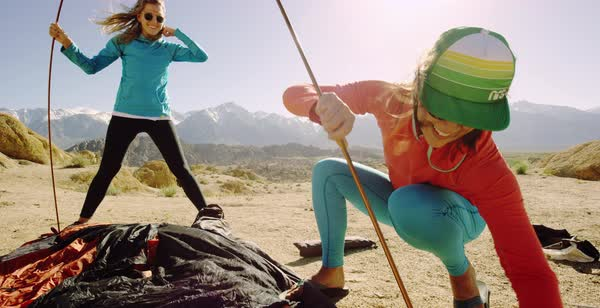 Hand-held shot of two women setting up a tent in Alabama Hills Royalty-free stock video