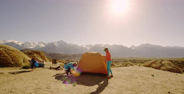 Static shot of two female hikers setting up a tent in blowing wind Royalty-free stock video