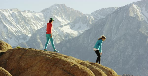Slow motion shot of three female hikers sitting down on a cliff Royalty-free stock video