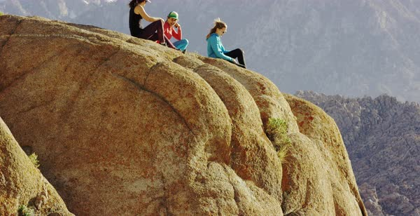 Tilt-up shot of three female hikers sitting on a rock in Alabama Hills Royalty-free stock video