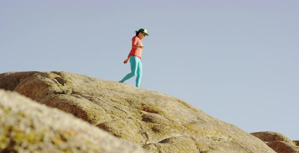 Tracking shot of a female hiker walking and jumping on rock formations Royalty-free stock video