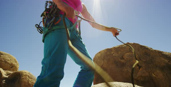 Hand-held shot of a woman preparing rope before rock climbing Royalty-free stock video