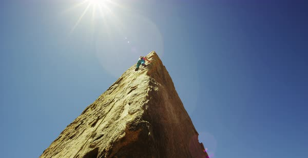 Panning shot of a woman climbing up a rock wall in Alabama Hills Royalty-free stock video