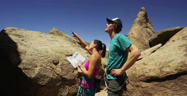 Hand-held shot of two rock climbers talking and looking at a book Royalty-free stock video