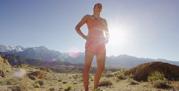 Static shot of a female runner standing in a rocky desert with hands on hips Royalty-free stock video