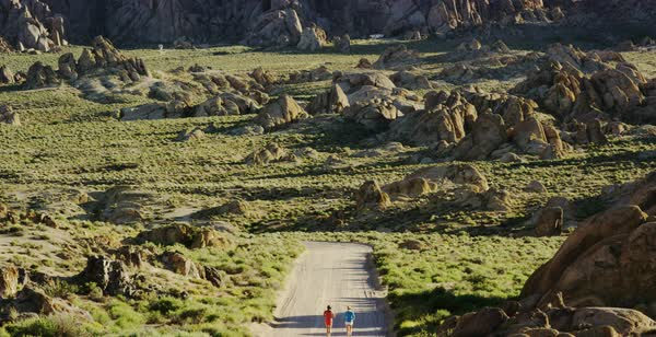 Static shot of two women running on a dirt road in Alabama Hills Royalty-free stock video