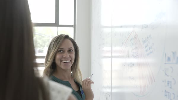 Hand-held shot view of a woman writing ideas on a whiteboard in an office Royalty-free stock video
