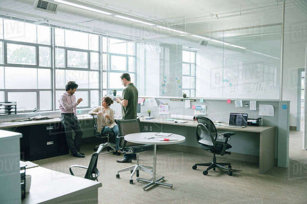 Three coworkers talking in an open plan office Royalty-free stock photo