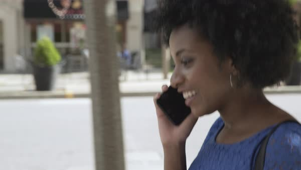 Tracking shot of a woman talking on a cell phone on a street Royalty-free stock video