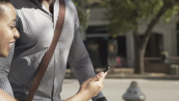 Gimbal shot of a couple looking at a cell phone while walking on a street Royalty-free stock video