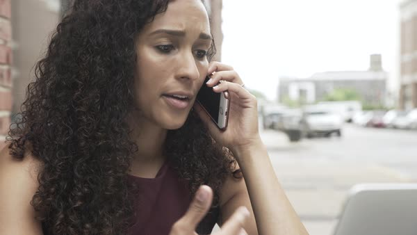 Gimbal shot of a woman talking on a cell phone while using a laptop Royalty-free stock video