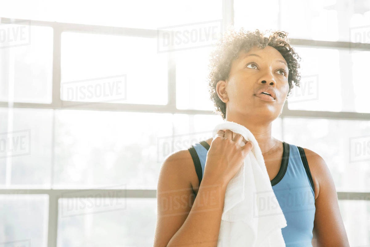 Woman wiping neck with towel after exercise Royalty-free stock photo