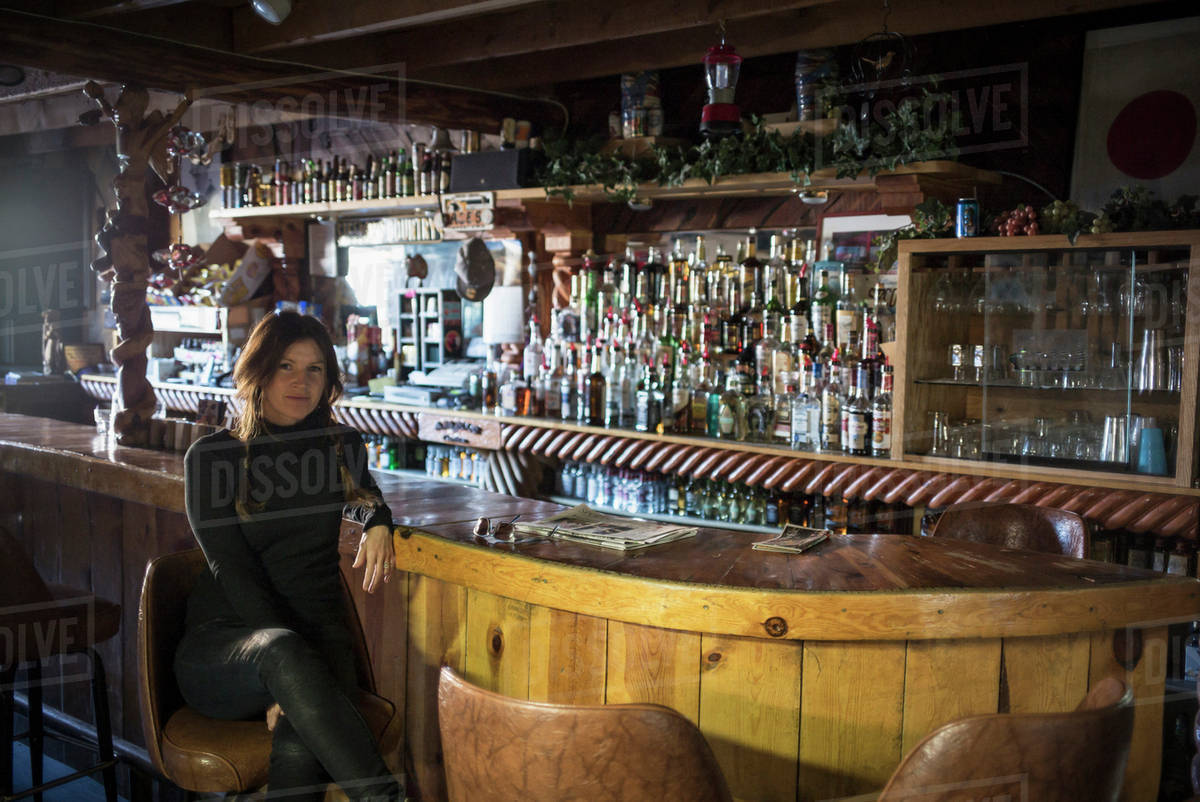 caucasian woman sitting in empty bar stock photo dissolve
