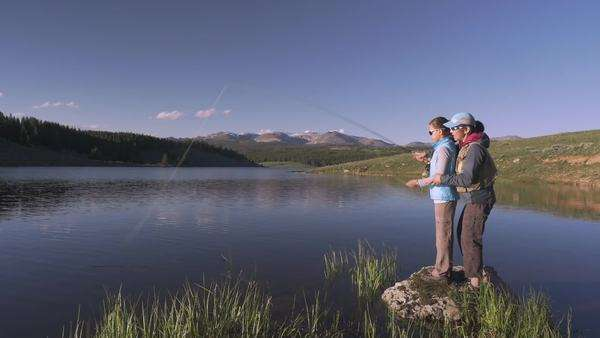 Mother teaching daughter fly fishing in river Royalty-free stock video